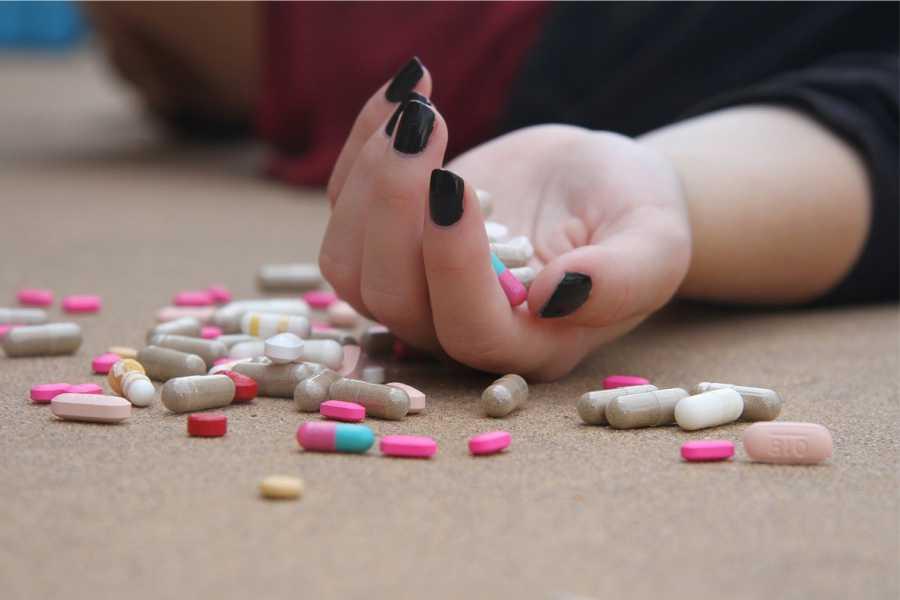 nő fekszik a földön a kezében tabletták