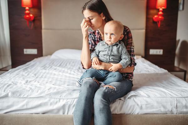 majka sa bebm u naručju sedi u krevetu sumorno