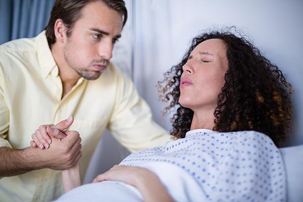 apas szülés folyamata a korházban, fogja kismama kezit mig vajudik